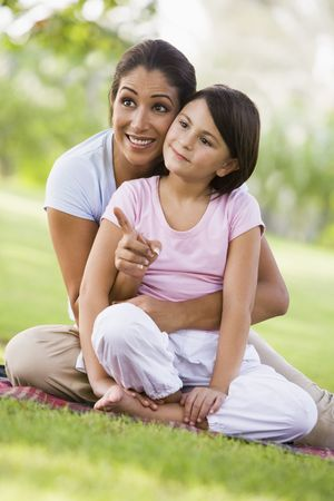 Mother and daughter outdoors in park pointing and smiling (selective focus) photo