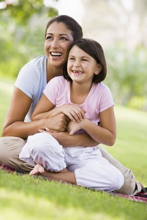 Mother and daughter outdoors in park smiling (selective focus) photo
