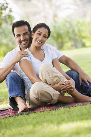 Couple sitting outdoors in park smiling (selective focus) Stock Photo - 3186635