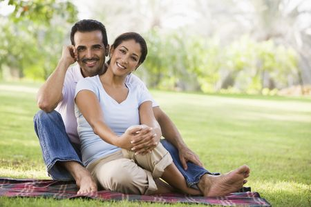 married couples: Couple sitting outdoors in park smiling (selective focus)