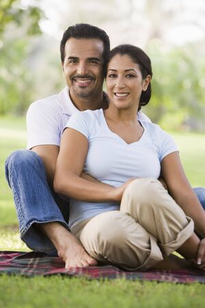 married couple: Couple sitting outdoors in park smiling (selective focus)