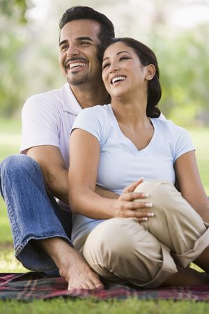 Couple sitting outdoors in park smiling (selective focus) photo