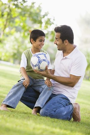 teaching adult: Father and son outdoors in park with ball smiling (selective focus)