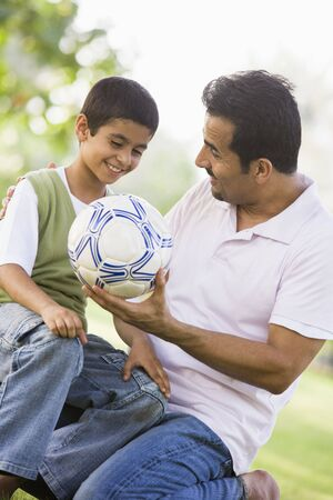 Father and son outdoors in park with ball smiling (selective focus) Stock Photo - 3186642