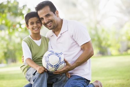 Father and son outdoors in park with ball smiling (selective focus) photo