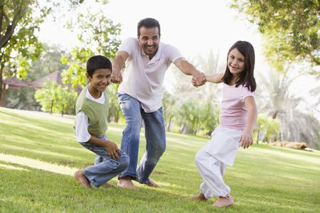 fatherhood: Two young children outdoors in park pulling smiling father by arms (selective focus) Stock Photo