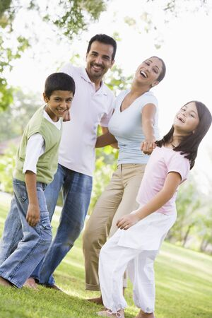 offset view: Family outdoors in park bonding and smiling (selective focus) Stock Photo