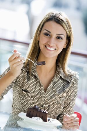 offset angle: Woman at restaurant eating dessert and smiling (selective focus)