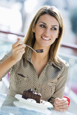 offset angles: Woman at restaurant eating dessert and smiling (selective focus)