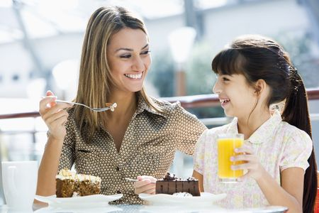 caucasoid race: Mother at restaurant with daughter eating dessert and smiling (selective focus)