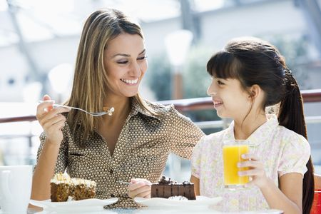 Mother at restaurant with daughter eating dessert and smiling (selective focus) photo