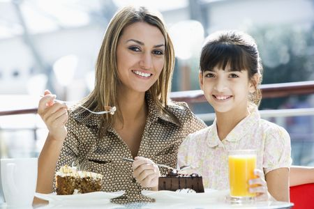 Mother at restaurant with daughter girl eating dessert and smiling (selective focus) photo