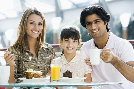 Familia restaurante a comer postre y sonriente (atención selectiva)