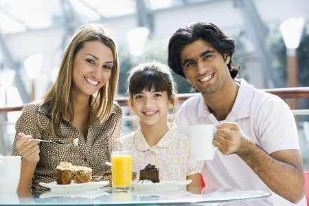 Family at restaurant eating dessert and smiling (selective focus) photo