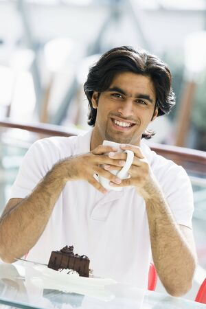 windowpanes: Man at restaurant eating dessert and smiling (selective focus)