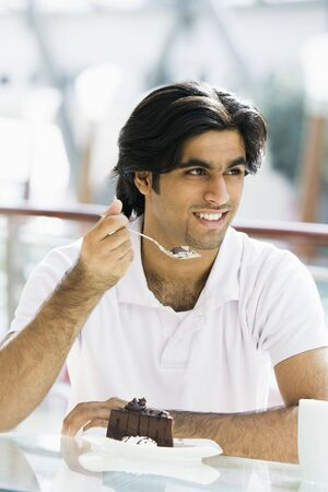 Man at restaurant eating dessert and smiling (selective focus) Stock Photo - 3186812