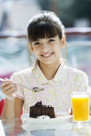 Young girl at restaurant eating dessert and smiling (selective focus) photo