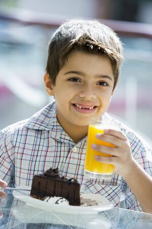 Young boy at restaurant eating dessert and smiling (selective focus) photo