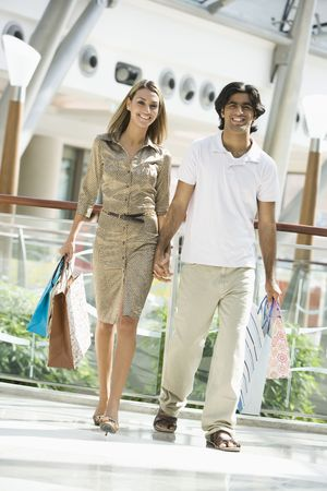 Couple walking in mall holding hands and smiling (selective focus) Stock Photo - 3186576