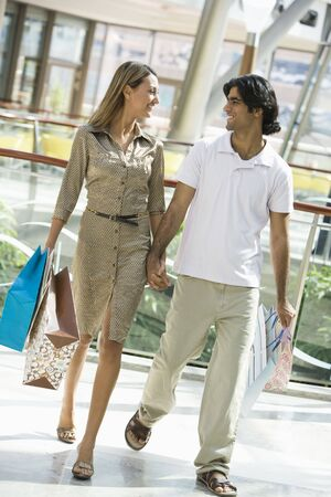 Couple walking in mall holding hands and smiling (selective focus) Stock Photo - 3186303