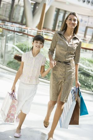 Mother and daughter walking in mall smiling (selective focus)