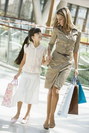 tweens: Mother and daughter walking in mall smiling (selective focus)