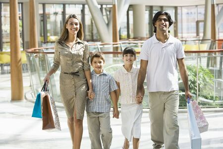 Family walking in mall holding hands and smiling (selective focus) Stock Photo - 3186297