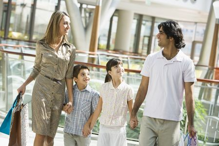 Family walking in mall holding hands and smiling (selective focus) photo