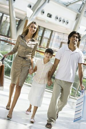 Family walking in mall holding hands and smiling (selective focus) Stock Photo - 3186312