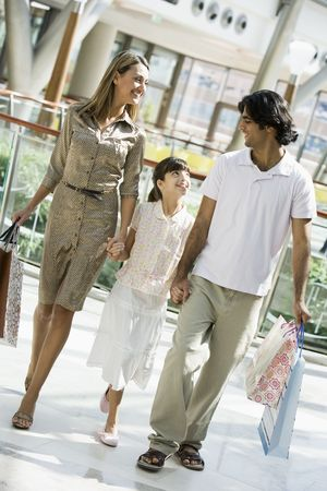 tweeny: Family walking in mall holding hands and smiling (selective focus)