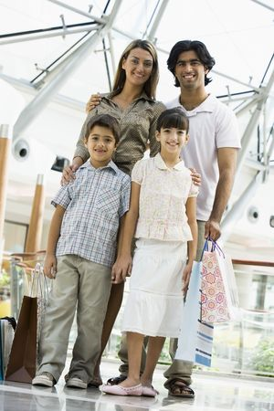 windowpanes: Family standing in mall smiling (selective focus)