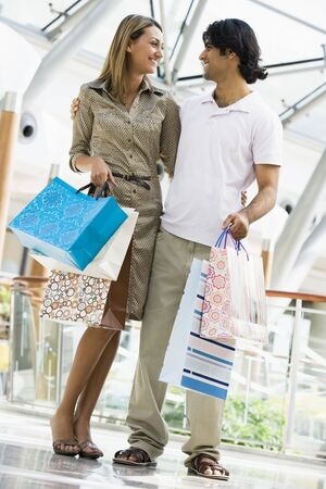 Couple standing in mall smiling (selective focus) photo