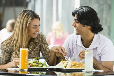adult sandwich: Couple at restaurant eating and smiling (selective focus)