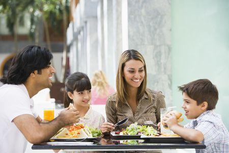 familia comiendo: Familia restaurante a comer y sonriente (atenci�n selectiva)