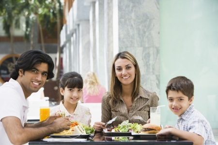 Family at restaurant eating and smiling (selective focus) photo