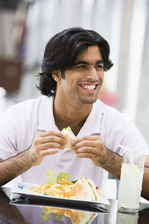 adult sandwich: Man at restaurant eating sandwich and smiling (selective focus)
