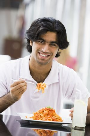 Man at restaurant eating spaghetti and smiling (selective focus) photo
