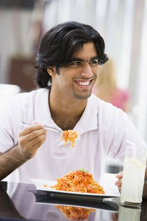 cuisines: Man at restaurant eating spaghetti and smiling (selective focus)