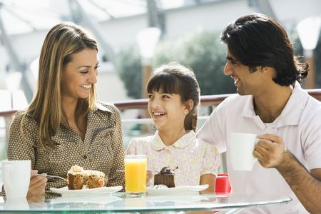 tweeny: Family at restaurant eating dessert and smiling (selective focus)