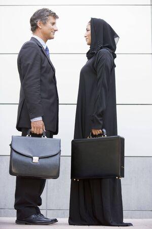 side profile: Due uomini d'affari in piedi all'aperto con valigie sorridente  Archivio Fotografico