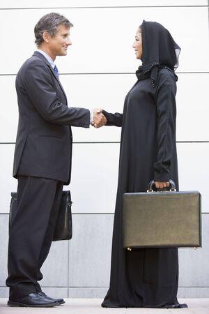 poign�es de main: Deux hommes d'affaires debout en plein air avec porte-documents et une poign�e de main en souriant Banque d'images