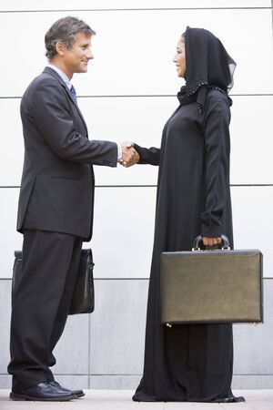 jilaabah: Two businesspeople standing outdoors with briefcases shaking hands and smiling