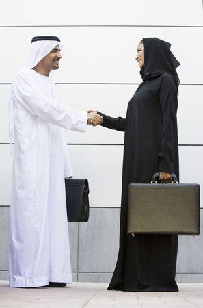 manos estrechadas: Dos hombres de negocios de pie al aire libre con maletines de agitar las manos y sonriendo