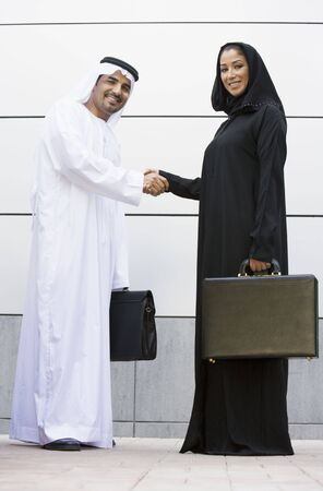 Two businesspeople standing outdoors with briefcases shaking hands and smiling photo