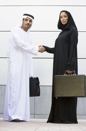 thawbs: Dos hombres de negocios de pie al aire libre con maletines de agitar las manos