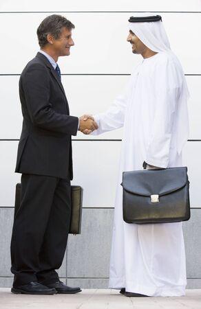 thawbs: Dos hombres de negocios de pie al aire libre con maletines de agitar las manos y sonriendo
