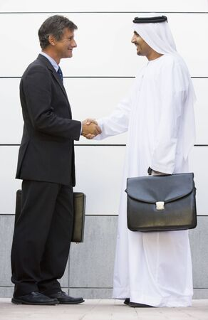 Two businessmen standing outdoors with briefcases shaking hands and smiling photo