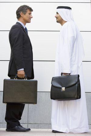 thawbs: Dos hombres de negocios de pie al aire libre con maletines