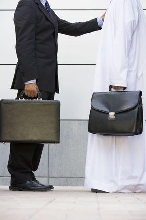 manos estrechadas: Dos hombres de negocios de pie al aire libre con maletines