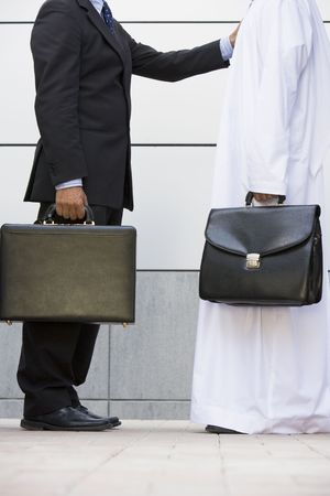 khameez: Two businessmen standing outdoors with briefcases